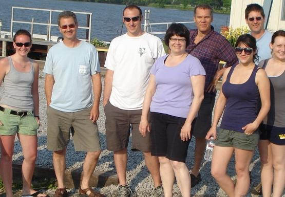 Eleven people stand for a picture near a boat launch.