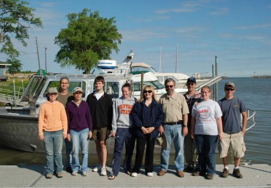 Ten people stand on a boat dock in front of a boat