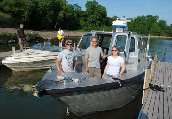 Three people stand for a picture at the front of a grey boat that's tied up to a dock.