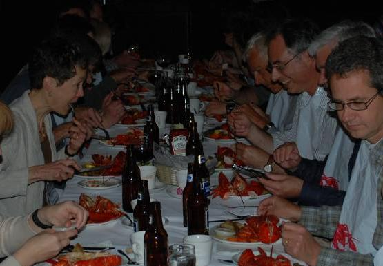 a long table of people eating lobster