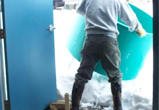 A person maneuvers a large round tank over a snow bank in the open doors of a room. There are exposed pipes on the floor.