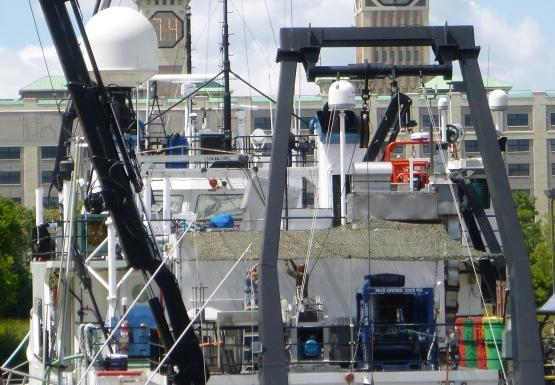 """A large white boat tied up at dock by a building with a clock tower. The boat is labeled """"Lake Guardian"""""""