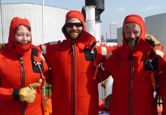 Four people in red survival suits on the deck of a large boat