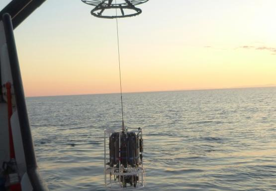 A large frame and winch is used to lower a device into the water off the side of a large boat