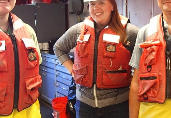 Three people inside wearing hard hats, life jackets, and rain pants.