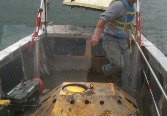 A person in the front of a boat. There are two large yellow devices on the deck and the frame at the front of the boat is lifting a third one.