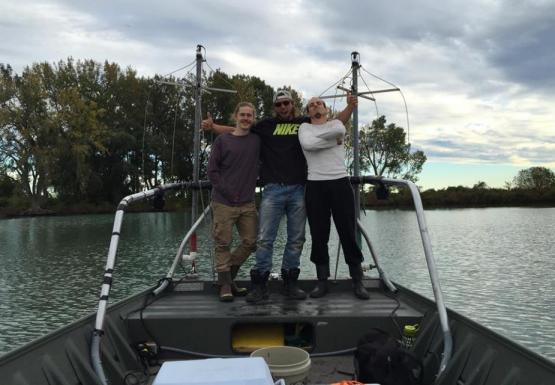 Three people posing for a picture at the front of a boat
