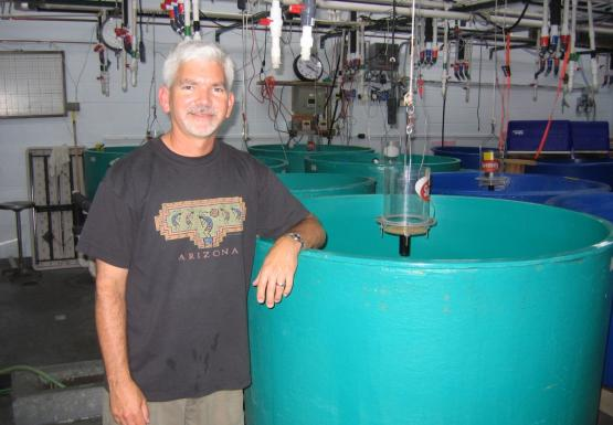 "A person stands with their arm resting on a round green tank in a lab. Their shirt says ""Arizona"""