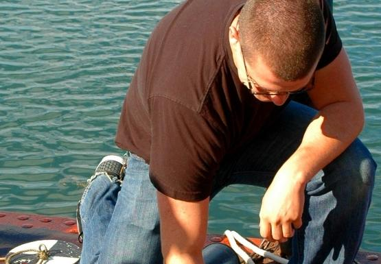 Student kneels down on the dock to examine something in a white pan