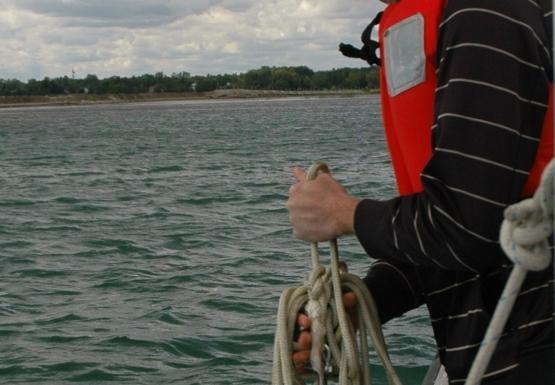 a student at the edge of the boat pulls up rope and sampling equipment