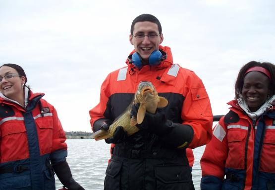 Three people in orange and blue float suits stand in front of the water. One is holding a medium-sized fish