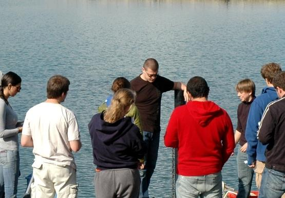 A group of people stand on a dock facing the water