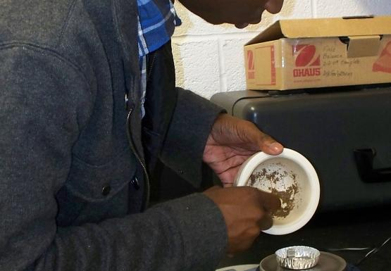 A person stands at a counter and scrapes a brown powder from a white dish into a metal tray on a scale
