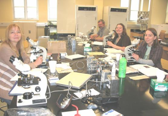Four people sit at microscopes on either side of a large lab table