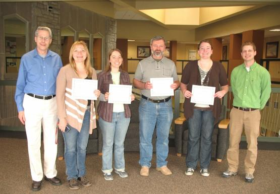 A group of six people posing for a picture. Four people hold up certificates
