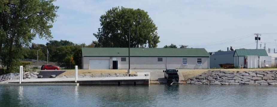 A white building with a green roof with a dock and boat launch, next to the water. A boat is backed into the water with a trailer.
