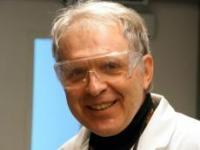 portrait of Alexander Nazarenko wearing safety glasses and a lab coat