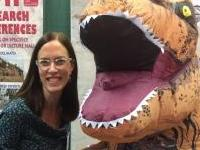 Camille Holmgren posing next to a t-rex mascot