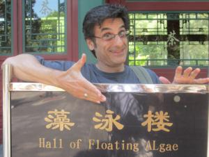 "Rick stands and gestures to a black sign with three yellow characters, translated to ""Hall of Floating Algae"""