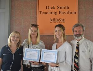 "Four people posing for a picture by a wall. The two in the center are holding certificates. A sign behind them says ""Dick Smith Teach Pavilion, Buffalo State."""