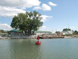 a large tree and some buildings with a dock and boat ramp at the edge of a body of water. A red navigation buoy is anchored near the dock