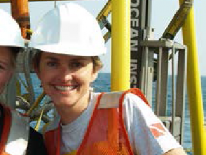 Elizabeth Hinchey Malloy in a life jacket and hard hat in front of equipment