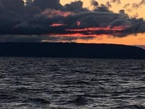 Grey clouds over the grey waters of Lake Superior at dusk. There is a dark strip of land just beneath the clouds.
