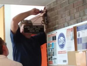 """A person watches as another person uses a screwdriver on a sign on the wall of a hallway near a bulletin board. The sign says """"Natural and Social Sciences Dean's Office Room A113."""""""