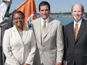 President Katherine Conway-Turner, State Senator Mark Grisanti, and Dean Mark Severson stand in front of a silver boat with an orange flag