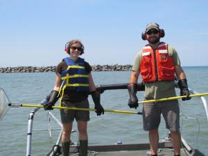two people wearing life jackets, gloves, and hearing protection stand at the front of a boat holding nets with long yellow poles