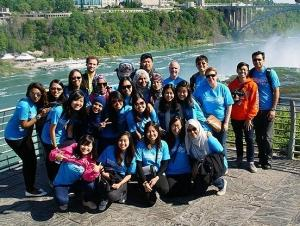 a group of people stand in front of a railing at Niagara Falls