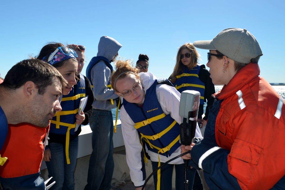 A group of students in life jackets look at a small gray instrument that an instructor holds up
