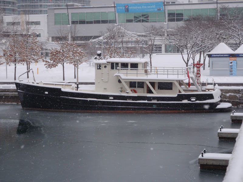 A color photo of a black & white boat docked in icy water in front of some buildings in a snowy city