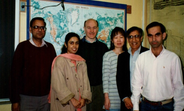 A color photo of six people standing in front of a map of the world in a classroom.