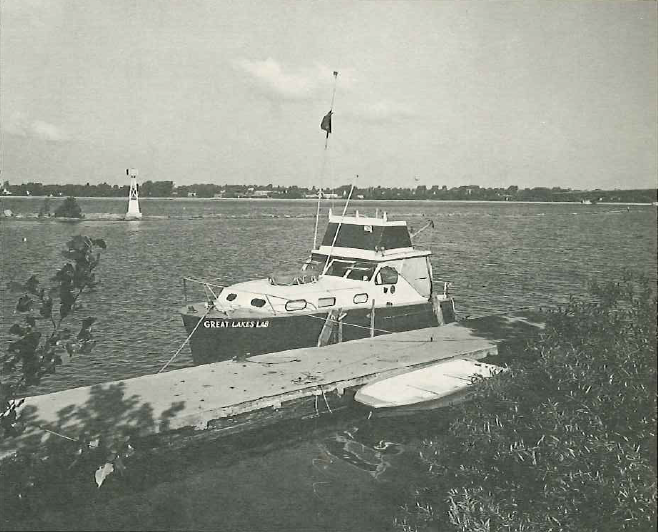 Black & white photo of a black & white boat tied up to a dock in the water