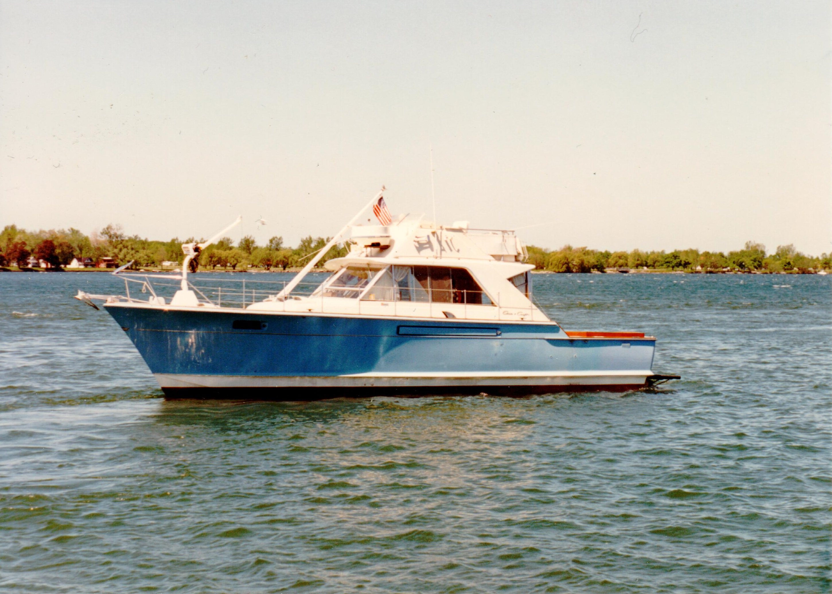 A photo of a blue and white boat facing left in the water.
