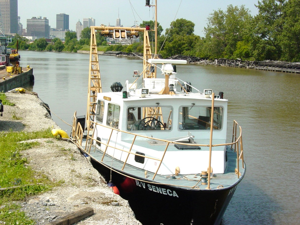 A black & white boat, docked in a canal in front of the Buffalo skyline. It has a yellow A-frame boom