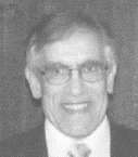 A black and white photo of a man wearing glasses, a suit, and a tie.