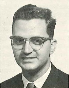 A black and white portrait of a man with dark hair and glasses in a suit and tie