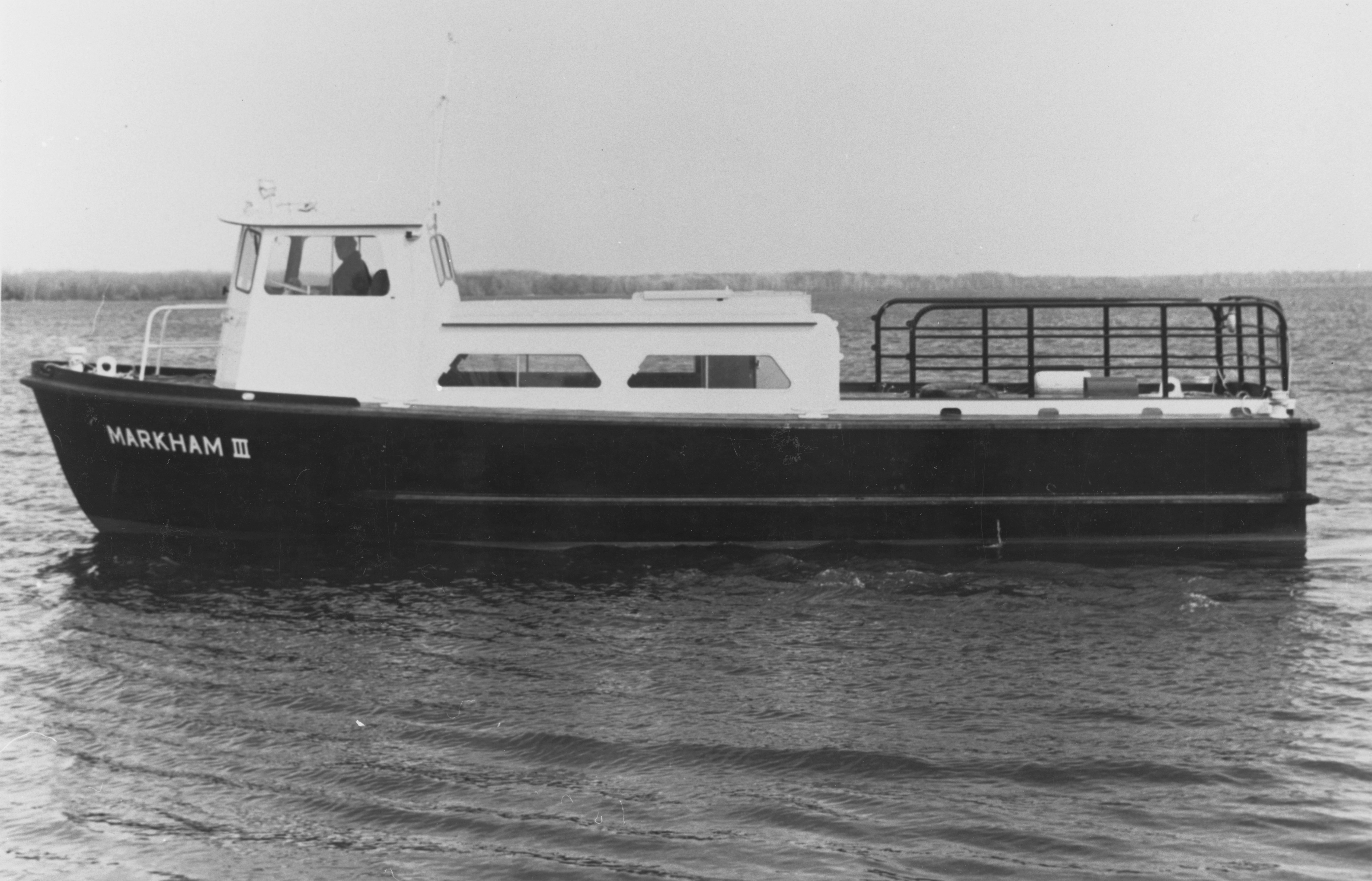 "Black & white photo of a black & white boat facing left. It says ""MARKHAM III"" in white on its bow."