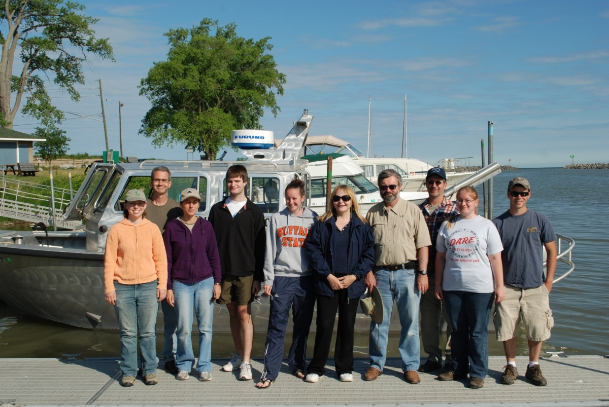 a group of people stand in front of a silver boat at a dock