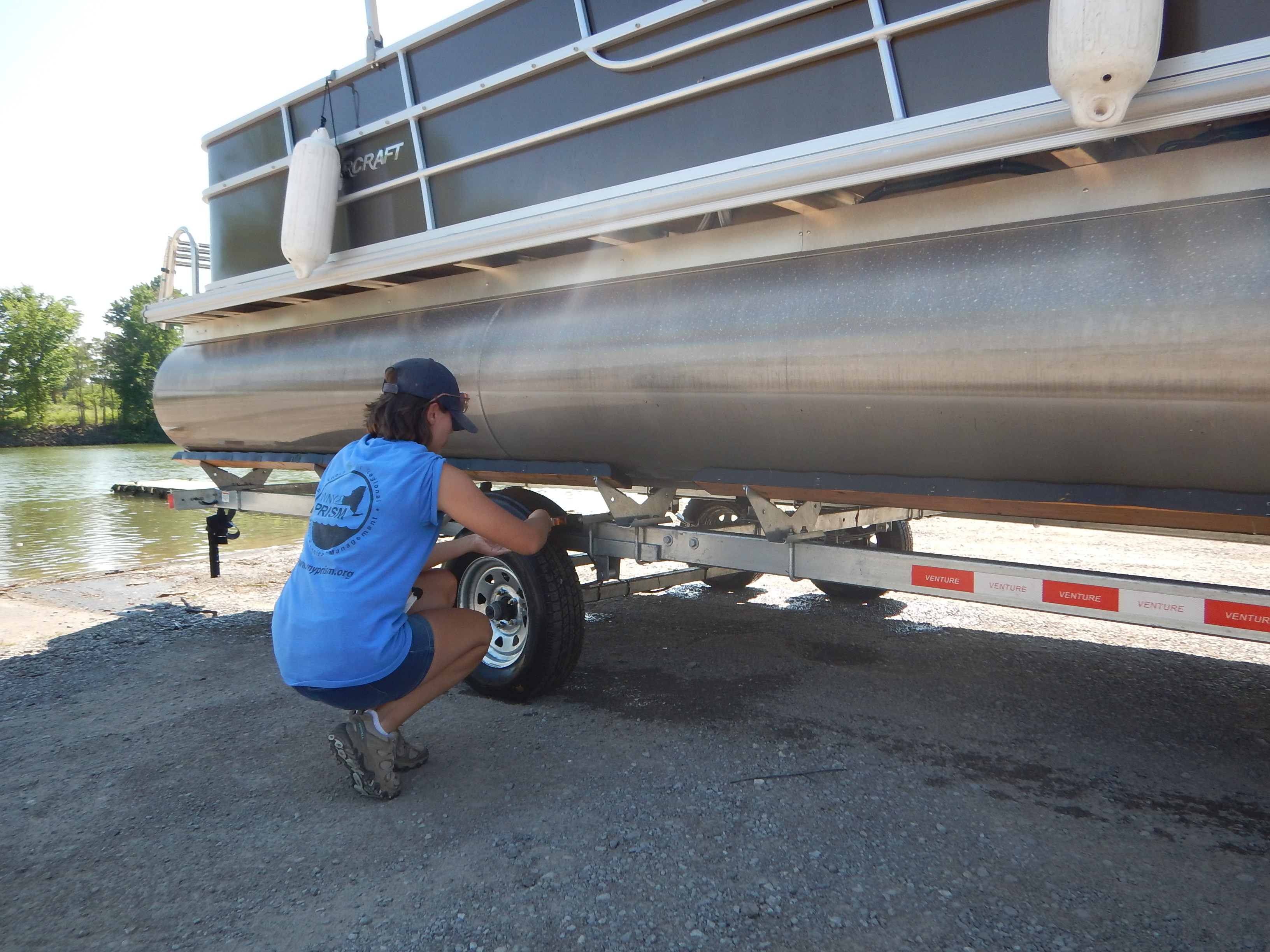 a person crouches by a boat on a trailer to inspect it