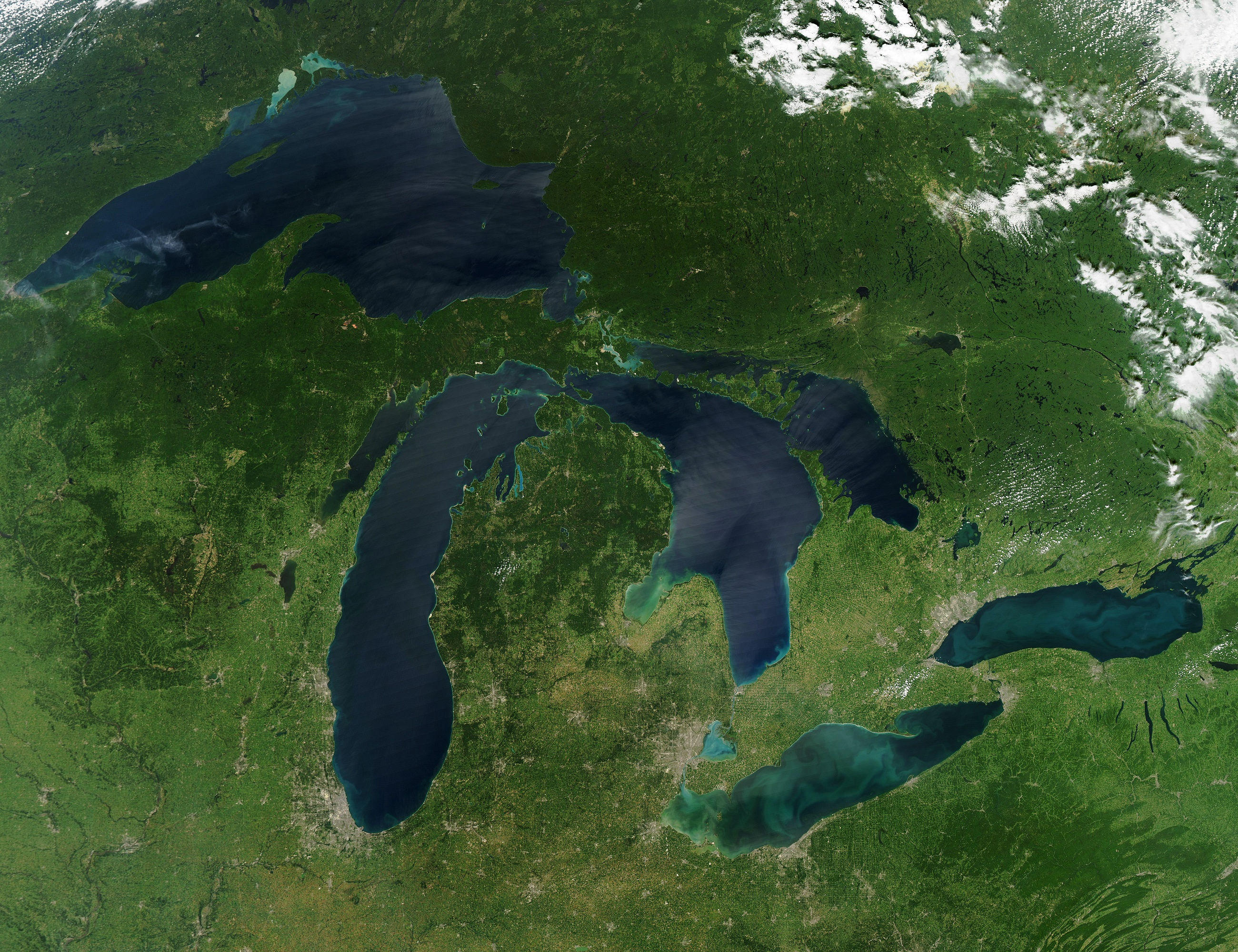 satellite image of the Great Lakes showing five blue lakes, green land, and white clouds