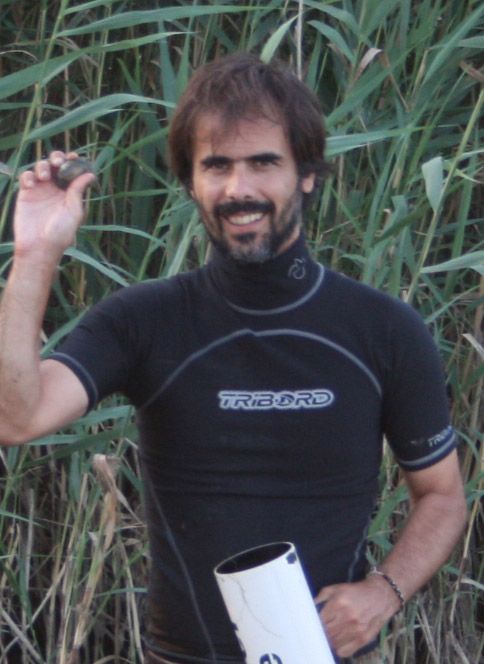 Manuel Lopes-Lima standing in front of tall grass, wearing a wet suit, and holding up a mussel.